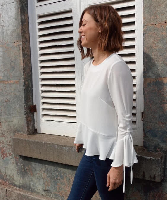 Miley Woven Top Sewing Pattern By Style Arc - Feminine, loose-fitting top featuring a high-low hem flounce and draw string sleeve.